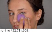 Купить «young woman with sponge applying makeup», видеоролик № 32711308, снято 8 декабря 2019 г. (c) Syda Productions / Фотобанк Лори