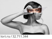 Купить «Girl covers her face with a shard of the mirror. Female with mirror shard in hand posing on gray background», фото № 32711344, снято 14 декабря 2019 г. (c) Serg Zastavkin / Фотобанк Лори