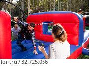 Men competing to collect hoops on inflatable arena. Стоковое фото, фотограф Яков Филимонов / Фотобанк Лори