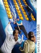 Купить «Friends climbing on inflatable slide in amusement park», фото № 32725068, снято 29 февраля 2020 г. (c) Яков Филимонов / Фотобанк Лори