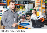Купить «Man with tools and woman seller at cash desk», фото № 32725132, снято 17 мая 2018 г. (c) Яков Филимонов / Фотобанк Лори