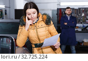Girl client is disappointed of tire replacement her car in workshop. Стоковое фото, фотограф Яков Филимонов / Фотобанк Лори