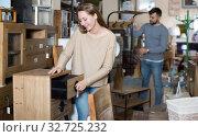 Купить «Girl choosing vintage bedside table», фото № 32725232, снято 9 ноября 2017 г. (c) Яков Филимонов / Фотобанк Лори