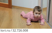 Шестимесячный ребенок учится переворачиваться лежа на полу в комнате. Стоковое видео, видеограф Кекяляйнен Андрей / Фотобанк Лори