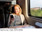 Купить «Businesswoman communicating on cellphone using headphone set while traveling by train in business class seat.», фото № 32731016, снято 28 мая 2020 г. (c) easy Fotostock / Фотобанк Лори