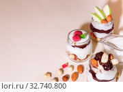 Купить «Sweet tasty milk curd creamy food in a glass jar of homemade breakfast. Cheesecake, English Trifle, Eton dessert, tiramisu, zuppa Inglese with nuts, almonds, cashews, hazelnuts, candied fruits and chocolate sauce», фото № 32740800, снято 14 декабря 2019 г. (c) Светлана Евграфова / Фотобанк Лори