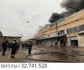 Купить «Пожарная команда тушит пожар на складе. Пожарный вертолет», фото № 32741528, снято 13 декабря 2019 г. (c) Кузнецов Максим / Фотобанк Лори