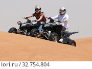 Купить «Dubai, United Arab Emirates, teenagers drive on quads through the desert», фото № 32754804, снято 30 марта 2018 г. (c) Caro Photoagency / Фотобанк Лори