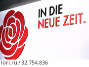Berlin, Germany - The motto of the federal party conference of the SPD, In DIe Neue Zeit, on the back wall of the stage. Next to it the red rose, the symbol of the SPD. Редакционное фото, агентство Caro Photoagency / Фотобанк Лори