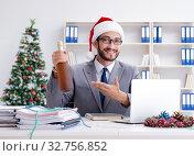 Купить «Young businessman celebrating christmas in the office», фото № 32756852, снято 22 июля 2017 г. (c) Elnur / Фотобанк Лори