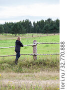 Mature grey-haired woman leans against fence in green grass and watches at pasture in summer time. Стоковое фото, фотограф Кекяляйнен Андрей / Фотобанк Лори