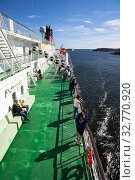 People are on upper side deck of cruise ferry boat. It is cruise liner of Viking line Finnish shipping company. Trip from Helsinki to Stockholm (2018 год). Редакционное фото, фотограф Кекяляйнен Андрей / Фотобанк Лори