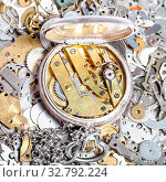 Купить «Watchmaker workshop - open retro silver pocket watch with brass clockwork on heap of clock spare parts», фото № 32792224, снято 29 января 2020 г. (c) easy Fotostock / Фотобанк Лори