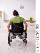 Купить «Young male invalid in wheel-chair suffering at home», фото № 32794180, снято 23 июля 2019 г. (c) Elnur / Фотобанк Лори
