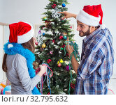 Купить «Young family decorating christmas tree on happy occasion», фото № 32795632, снято 21 июля 2017 г. (c) Elnur / Фотобанк Лори