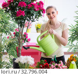 Young woman watering plants in her garden. Стоковое фото, фотограф Elnur / Фотобанк Лори