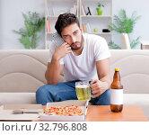 Купить «Man eating pizza having a takeaway at home relaxing resting», фото № 32796808, снято 18 июля 2017 г. (c) Elnur / Фотобанк Лори