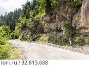 Купить «Dirt road in the mountains along the cliffs», фото № 32813688, снято 13 июня 2019 г. (c) Евгений Ткачёв / Фотобанк Лори