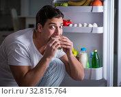 Man at the fridge eating at night. Стоковое фото, фотограф Elnur / Фотобанк Лори
