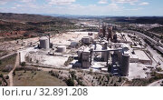 Купить «Aerial view of a huge cement plant with warehouses in Bunol, Valencia, Spain», видеоролик № 32891208, снято 24 апреля 2019 г. (c) Яков Филимонов / Фотобанк Лори