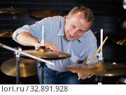 Купить «Musician male choosing drum set», фото № 32891928, снято 18 сентября 2017 г. (c) Яков Филимонов / Фотобанк Лори