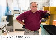 Купить «Portrait of elderly foreman in protective gloves standing in workshop», фото № 32891988, снято 24 февраля 2020 г. (c) Яков Филимонов / Фотобанк Лори