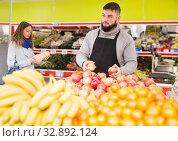 Купить «Supermarket employee will lay out ripe pomegranates on the counter», фото № 32892124, снято 20 ноября 2019 г. (c) Яков Филимонов / Фотобанк Лори