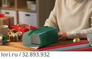 Купить «woman wrapping christmas gift into paper at home», видеоролик № 32893932, снято 18 декабря 2019 г. (c) Syda Productions / Фотобанк Лори
