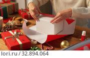 Купить «woman wrapping christmas gift into paper at home», видеоролик № 32894064, снято 18 декабря 2019 г. (c) Syda Productions / Фотобанк Лори