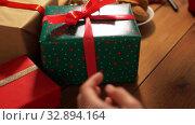 Купить «hands stacking packed christmas gifts on table», видеоролик № 32894164, снято 18 декабря 2019 г. (c) Syda Productions / Фотобанк Лори