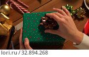 Купить «hands packing christmas gift and choosing bow», видеоролик № 32894268, снято 18 декабря 2019 г. (c) Syda Productions / Фотобанк Лори