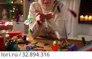 Купить «woman with confetti and christmas gifts at home», видеоролик № 32894316, снято 18 декабря 2019 г. (c) Syda Productions / Фотобанк Лори