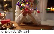 Купить «woman with confetti and christmas gifts at home», видеоролик № 32894324, снято 18 декабря 2019 г. (c) Syda Productions / Фотобанк Лори