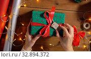 Купить «hands holding christmas gift with name tag», видеоролик № 32894372, снято 18 декабря 2019 г. (c) Syda Productions / Фотобанк Лори