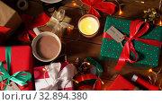 Купить «christmas gifts, candle, coffee and garland lights», видеоролик № 32894380, снято 18 декабря 2019 г. (c) Syda Productions / Фотобанк Лори