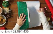 Купить «hands wrapping christmas gift into paper at home», видеоролик № 32894436, снято 18 декабря 2019 г. (c) Syda Productions / Фотобанк Лори