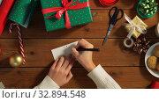 Купить «hands attaching name tag to christmas gift», видеоролик № 32894548, снято 18 декабря 2019 г. (c) Syda Productions / Фотобанк Лори