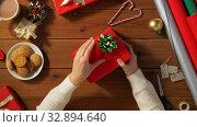 Купить «woman wrapping christmas gift into paper at home», видеоролик № 32894640, снято 18 декабря 2019 г. (c) Syda Productions / Фотобанк Лори