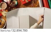 Купить «hands wrapping christmas gift into paper at home», видеоролик № 32894780, снято 18 декабря 2019 г. (c) Syda Productions / Фотобанк Лори