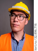 Studio shot of young Asian man construction worker wearing eyeglasses against gray background. Стоковое фото, фотограф Zoonar.com/Toni Rantala / easy Fotostock / Фотобанк Лори