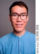 Studio shot of young Asian businessman wearing eyeglasses against gray background. Стоковое фото, фотограф Zoonar.com/Toni Rantala / easy Fotostock / Фотобанк Лори