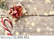 Купить «Christmas. Gift box with a red bow, a fluffy branch of a Xmas tree and Xmas Candy Cane on a wooden background with copy space, Top view. Copy space.», фото № 32899452, снято 31 марта 2020 г. (c) easy Fotostock / Фотобанк Лори