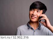 Studio shot of young Asian man using mobile phone against gray background. Стоковое фото, фотограф Zoonar.com/Toni Rantala / easy Fotostock / Фотобанк Лори