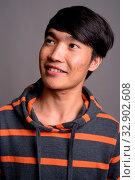 Studio shot of young Asian man wearing striped hoodie against gray background. Стоковое фото, фотограф Zoonar.com/Toni Rantala / easy Fotostock / Фотобанк Лори