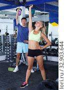 Купить «Couple during weightlifting workout», фото № 32903644, снято 16 июля 2018 г. (c) Яков Филимонов / Фотобанк Лори