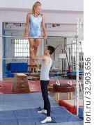 Купить «Man and woman doing acrobatic exercises in gym», фото № 32903656, снято 18 июля 2018 г. (c) Яков Филимонов / Фотобанк Лори