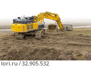 Yellow excavator at a loamy construction site, partly isolated in white back. Стоковое фото, фотограф Zoonar.com/PRILL Mediendesign Fotografie / easy Fotostock / Фотобанк Лори