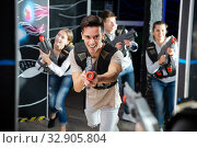Guy aiming laser gun during lasertag game. Стоковое фото, фотограф Яков Филимонов / Фотобанк Лори