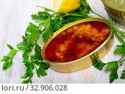 Купить «Tinned cod in tomato sauce on background with greens and lemon», фото № 32906028, снято 23 февраля 2020 г. (c) Яков Филимонов / Фотобанк Лори