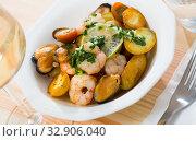 Tasty warm salad with fried potatoes, shrimp and mussels, served at plate. Стоковое фото, фотограф Яков Филимонов / Фотобанк Лори